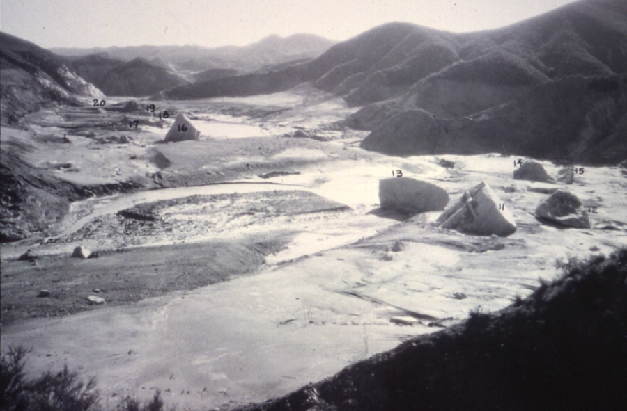 View looking downstream at concrete dam fragments that were carried from and settled downstream of the original dam site. Note height along valley slopes in which vegetation has been removed by floodwaters
